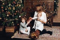 Mãe com as duas crianças na árvore de Natal foto de stock royalty free
