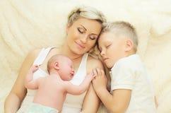 Mãe com as duas crianças que dormem junto na cama em casa Fotografia de Stock