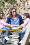 Mãe com as duas meninas no campo de jogos Fotos de Stock Royalty Free