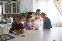 Mãe com as três crianças na cozinha que prepara cookies imagens de stock royalty free