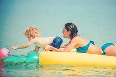 Mãe com a bola do jogo do filho na água Família feliz no mar das caraíbas Abacaxi inflável ou colchão de ar Férias de verão imagens de stock