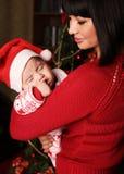 Mãe com cabelo escuro com o bebê pequeno bonito ao lado da árvore de Natal Imagens de Stock