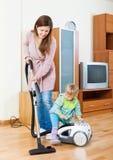Mãe com casa da limpeza da criança Foto de Stock Royalty Free