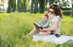 Mãe com contos de fadas encaracolado da leitura do penteado para o bebê Imagem de Stock