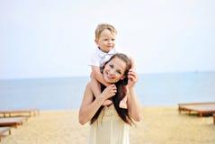 Mãe com a criança em arenoso ao seacoast Foto de Stock Royalty Free