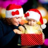 A mãe com criança pequena abre a caixa com os presentes no Natal Fotos de Stock Royalty Free
