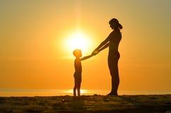 A mãe com criança senta-se na praia no por do sol Imagem de Stock