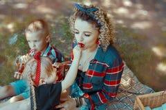 A mãe com crianças esating bagas frescas fotografia de stock royalty free