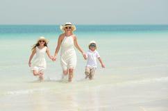 A mãe com crianças tem o divertimento na praia Fotos de Stock Royalty Free