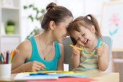 A mãe com divertimento pequeno da filha cortou o papel colorido das tesouras foto de stock