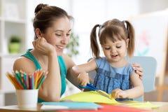 A mãe com divertimento pequeno da filha cortou o papel colorido das tesouras imagem de stock