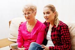 Mãe com a filha adulta que olha o filme triste Fotografia de Stock