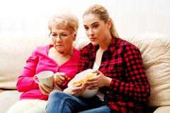 Mãe com a filha adulta que olha o filme triste Foto de Stock