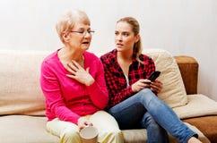 Mãe com a filha adulta que olha o filme triste Imagens de Stock