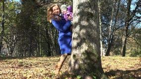 Mãe com a filha do bebê que esconde atrás da árvore no parque do outono 4K video estoque