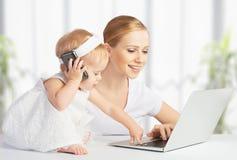 A mãe com filha do bebê trabalha com um computador e um telefone Imagens de Stock