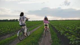 A mãe com a filha em bicicletas monta em uma estrada de terra vídeos de arquivo