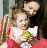Mãe com filha junto na cama que sorri, fim feliz da família fotografia de stock