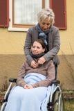 Mãe com a filha na cadeira de rodas imagem de stock royalty free