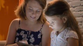 Mãe com a filha pequena que datilografa na tabuleta, sentando-se no sofá em casa, conceito de família dentro video estoque