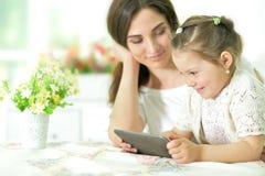 Mãe com a filha pequena que usa a tabuleta Fotografia de Stock Royalty Free