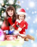 Mãe com a filha perto da árvore de Natal Foto de Stock