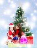 Mãe com a filha perto da árvore de Natal Fotos de Stock Royalty Free