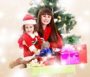 Mãe com a filha perto da árvore de Natal Fotos de Stock