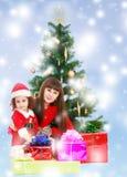 Mãe com a filha perto da árvore de Natal Imagem de Stock