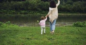 Mãe com a filha que corre às mãos do rio e da posse momentos felizes da maternidade Fundo das montanhas Moinho de vento sobre video estoque