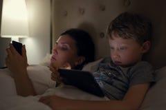 A mãe com filho olha em seus dispositivos eletrónicos que encontram-se na cama Foto de Stock Royalty Free