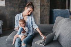 Mãe com funcionamento remoto do bebê e portátil da utilização durante a conversação no smartphone fotografia de stock