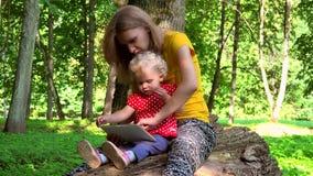 A mãe com a menina da filha da criança que usa o tablet pc senta-se no tronco de árvore caído filme