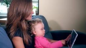 A mãe com a menina em joelhos olha o álbum de fotos da família no tela de computador vídeos de arquivo
