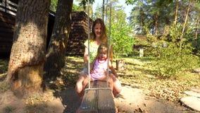 Mãe com a menina no balanço de madeira sob a árvore video estoque