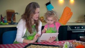 Mãe com a menina pequena bonito da filha que estuda a receita das cookies no tablet pc vídeos de arquivo