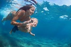 Mãe com a nadada da criança subaquática na associação azul da praia fotografia de stock
