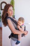 Mãe com o bebê na mochila frontal fotografia de stock royalty free