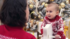 Mãe com o bebê no brinquedo de balanço dos cervos durante a Noite de Natal video estoque