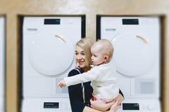 mãe com o bebê no fundo das máquinas de lavar foto de stock