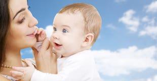 Mãe com o bebê sobre o fundo do céu fotografia de stock royalty free