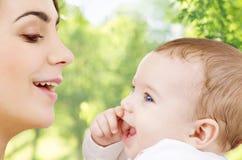 Mãe com o bebê sobre o fundo natural verde fotos de stock