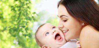 Mãe com o bebê sobre o fundo natural verde imagem de stock