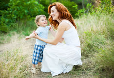 Mãe com o cabelo vermelho encaracolado longo que joga com seu filho no parque Imagem de Stock Royalty Free