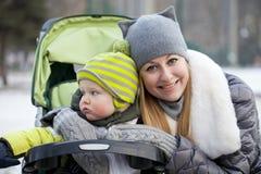 Mãe com o filho da criança de dois anos no parque do inverno Imagem de Stock