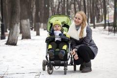 Mãe com o filho da criança de dois anos no parque do inverno Fotos de Stock Royalty Free