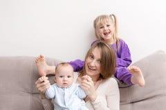 Mãe com o filho e a filha que têm o divertimento no sofá Sorriso e povos alegres Conceito de família feliz foto de stock