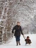 Mãe com o filho no parque do inverno com trenó Imagens de Stock