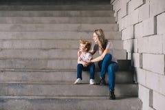 Mãe com o filho que senta no escadas Imagens de Stock Royalty Free