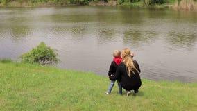 Mãe com o filho que senta-se na grama perto do lago e que acena a alguém a mão vídeos de arquivo